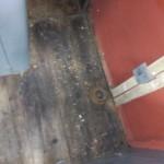 Původní dřevěná podlaha. V pravé části odkrytý bok stanoviště, kde byla odstraněna stará tepelná izolace a kov obroušen a natřen základní barvou.